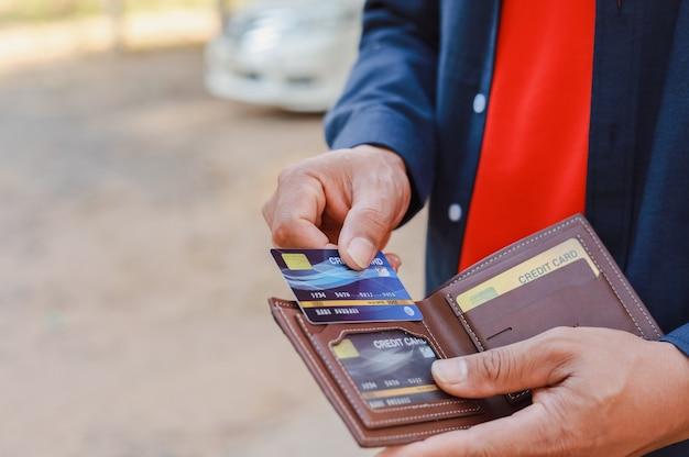 Um homem segurando um telefone, cartão de crédito e carteira