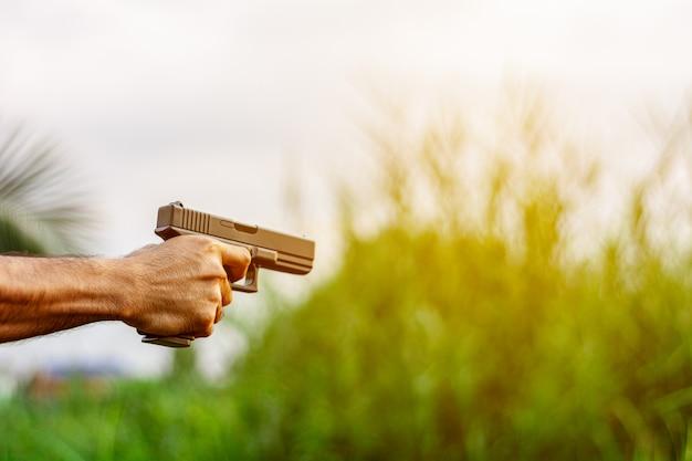 Um homem segurando uma arma na mão. - conceito de violência e crime.