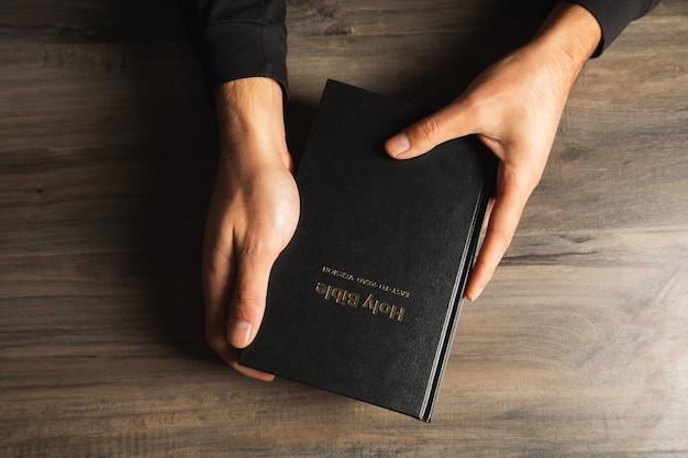 Um homem segurando uma bíblia à mesa. vista de cima