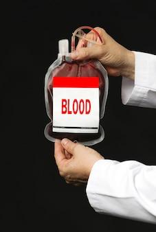 Um homem segurando uma bolsa de transfusão de sangue