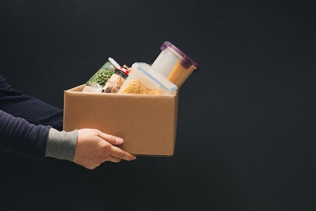 Um homem segurando uma caixa de doação de diferentes produtos no escuro