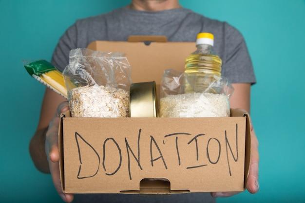Um homem segurando uma caixa de doação de diferentes produtos