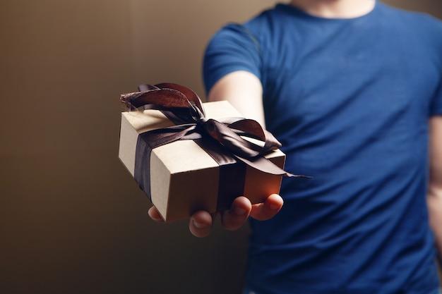 Um homem segurando uma caixa de presente na mão. no fundo marrom