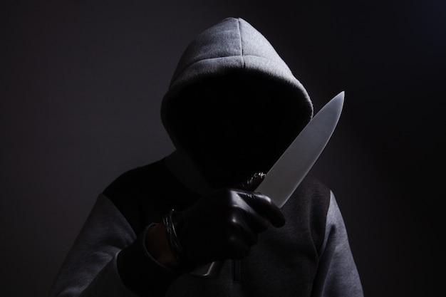 Um homem segurando uma grande faca ameaça