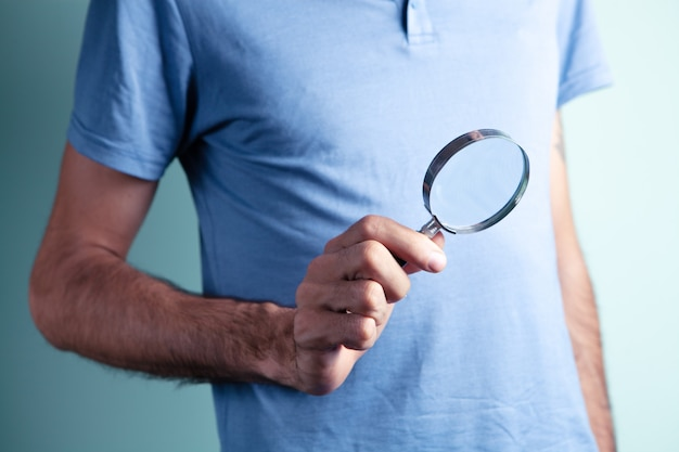 Um homem segurando uma lupa