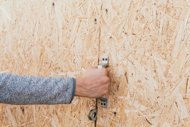 Um homem segurando uma maçaneta de uma porta de madeira