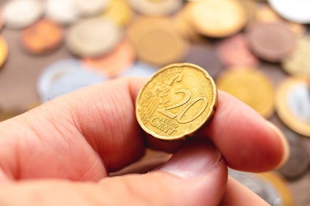 Um homem segurando uma moeda de vinte cêntimos em euros