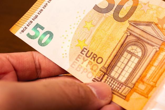 Um homem segurando uma nota de 50 euros para negócios de finanças e conceitos de ganhar dinheiro