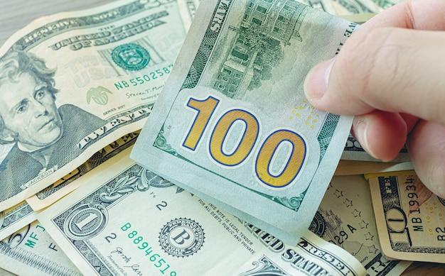 Um homem segurando uma nota de cem dólares entre outras notas