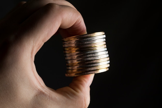 Um homem segurando uma pilha de moedas