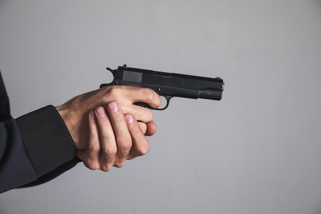 Um homem segurando uma pistola preta na mão ameaçando