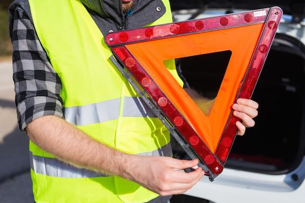 Um homem segurando uma placa triangular de um acidente