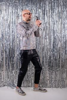 Um homem sem cabelo com óculos de sol em uma camisa brilhante, calça de couro preta e tênis cinza canta em um pequeno microfone prateado.