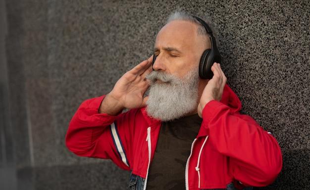 Um homem sênior barbudo na moda, ouvindo música ao ar livre. moda homem maduro.