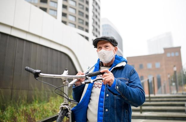 Um homem sênior carregando bicicleta ao ar livre na rua na cidade, o conceito de coronavírus.