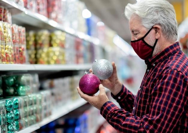 Um homem sênior de cabelo branco segurando duas bolas de natal brilhantes, prateadas e roxas, usando uma máscara médica devido a uma infecção por coronavírus