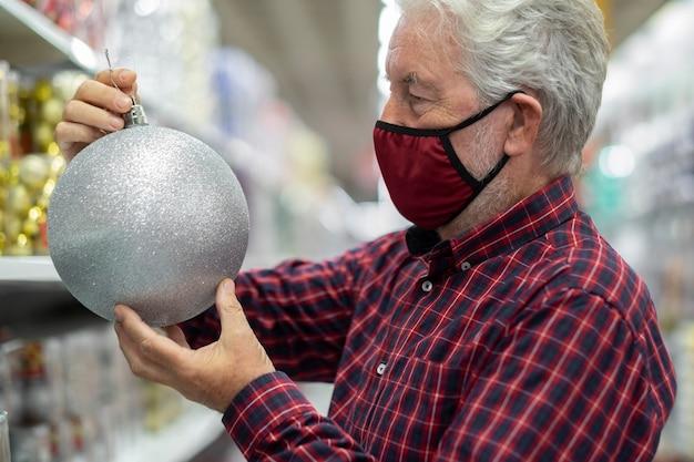 Um homem sênior de cabelo branco segurando uma grande bola de natal prata brilhante em uma loja, usando uma máscara médica devido a uma infecção por coronavírus