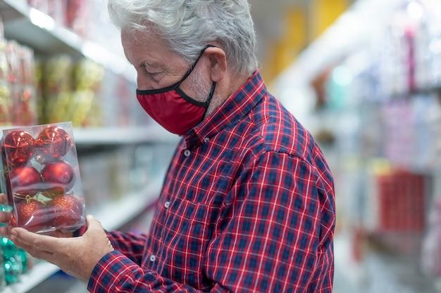Um homem sênior de cabelos brancos, usando uma máscara médica devido a uma infecção por coronavírus, escolhendo algumas bolas de natal em uma loja. novo conceito normal