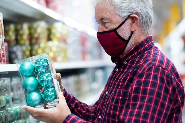 Um homem sênior de cabelos brancos, usando uma máscara médica devido a uma infecção por coronavírus, escolhendo uma bola de natal em uma loja. novo conceito normal