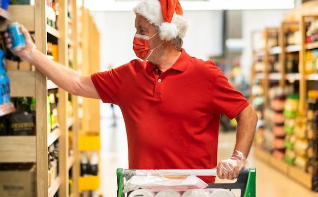 Um homem sênior no supermercado com chapéu de natal escolhe produtos para a casa fazendo compras no supermercado