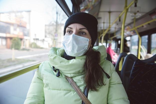 Um homem senta-se em um ônibus da cidade com uma máscara de proteção médica. proteção contra o coronavírus sars-cov-2 em transporte público.