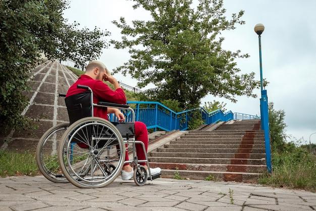 Um homem senta-se em uma cadeira de rodas, enfrenta dificuldades sozinho, depressão. o conceito de cadeira de rodas, pessoa com deficiência, vida plena, paralítico, pessoa com deficiência, cuidados de saúde.