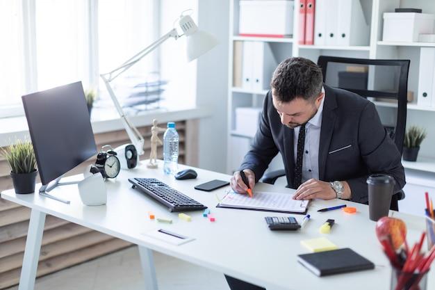 Um homem senta-se no escritório à mesa e trabalha com um marcador e documentos.