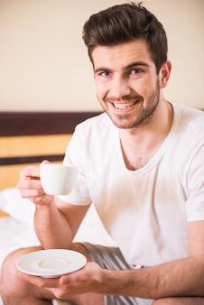 Um homem senta-se no quarto e bebe café da manhã.