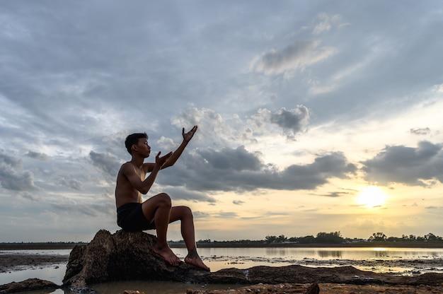 Um homem sentado dobrou os joelhos, fez um símbolo para pedir chuva na base das árvores e cercado por água.