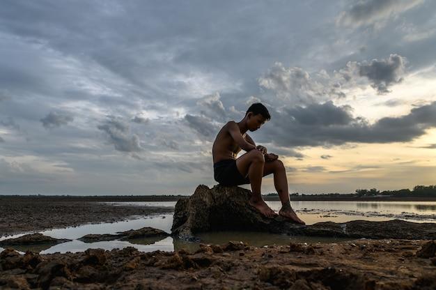 Um homem sentado dobrou os joelhos na base da árvore, onde o chão estava seco e as mãos colocadas na cabeça.