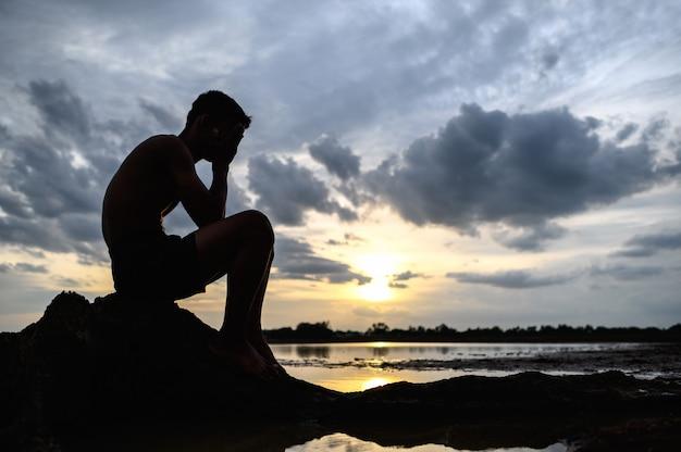 Um homem sentado dobrou os joelhos, segurando as mãos no rosto, na base da árvore, e havia água ao redor.