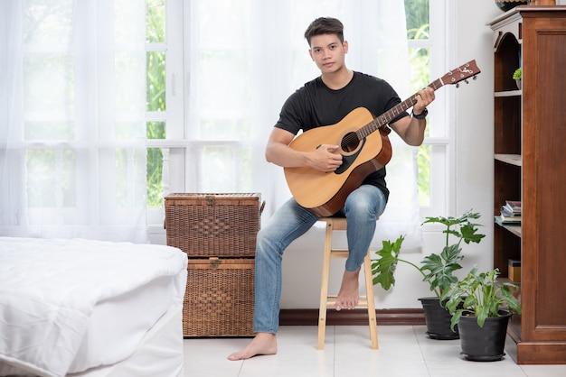 Um homem sentado e tocando violão em uma cadeira.