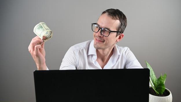 Um homem sentado em frente ao computador ganha dinheiro
