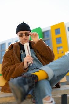 Um homem sentado em um banco com as pernas cruzadas na altura do joelho