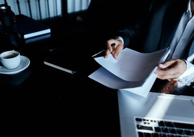 Um homem sentado em um café em frente a um laptop trabalhando com tecnologia de internet