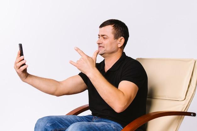 Um homem sentado em uma poltrona de couro se comunica não verbalmente por vídeo comunicação, mostrando que