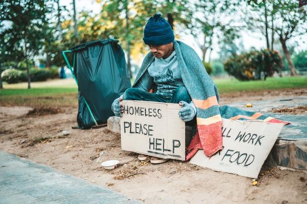 Um homem sentado mendigos com sem-teto, por favor, ajude a mensagem.