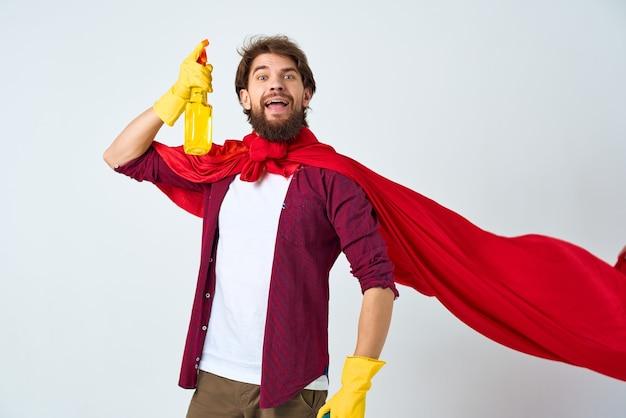 Um homem sentado no chão com uma capa vermelha para lavar acessórios, higiene, cuidados domésticos