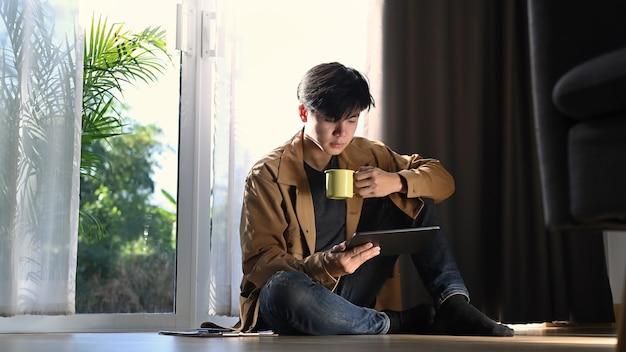 Um homem sentado no chão, segurando o café e olhando no tablet digital.