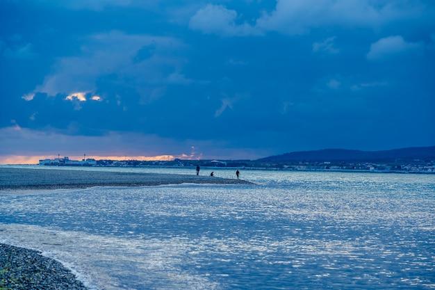 Um homem sentado sozinho em uma praia de seixos ao pôr do sol.