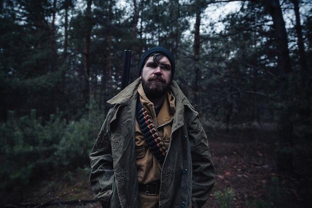 Um homem sério com um caçador de barba em um chapéu escuro e jaqueta cáqui em uma longa capa com uma arma no ombro está em uma floresta escura