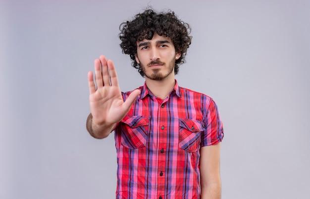 Um homem sério e bonito com cabelo encaracolado e camisa xadrez de mãos dadas ou gesto suficiente