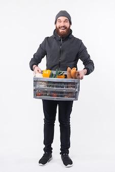 Um homem simpático segurando uma caixa com mantimentos prontos para entregá-los e sorrindo está olhando