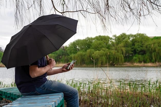 Um homem sob um guarda-chuva se senta em um banco na margem de um lago e usa seu smartphone
