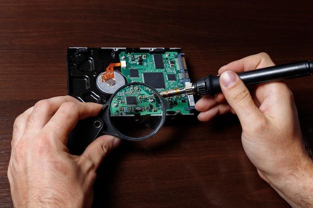 Um homem soldando um ferro de solda no disco rígido do computador