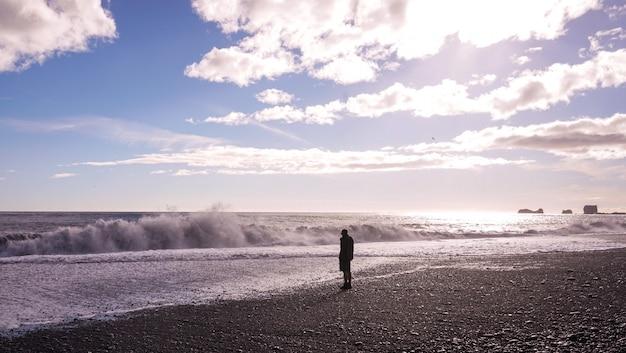 Um homem solitário em pé na praia