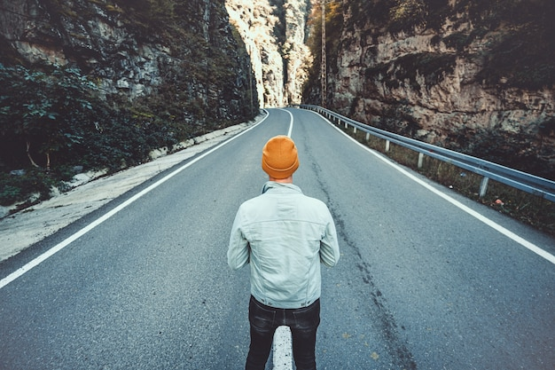 Um homem solitário fica na estrada entre as rochas nas montanhas.