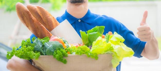 Um homem sorridente, bom e rápido entrega produtos de mercearia na casa do cliente, compras online durante quarentena coronavírus covid-19, comida em saco de papel ecológico, trabalhando com o coração