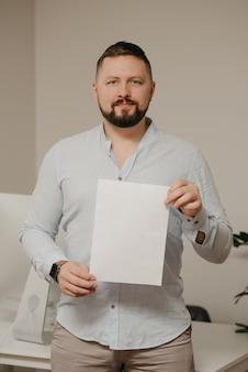 Um homem sorridente com barba está parado com uma folha de papel em branco perto de um computador desktop de aço em casa