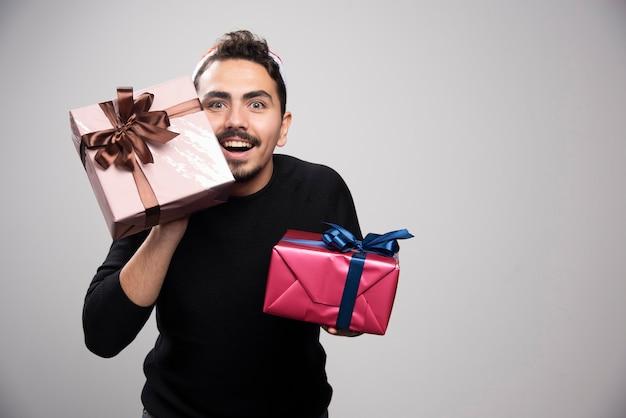 Um homem sorridente com um chapéu de papai noel segurando presentes de ano novo.